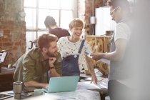 Réunion des concepteurs, discuter des plans à l'ordinateur portable dans l'atelier — Photo de stock