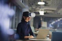 Mujer de negocios utilizando simulador de realidad virtual en el ordenador portátil en la oficina oscura - foto de stock