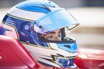 Primer plano fórmula un piloto de carreras de coches en el casco mirando hacia otro lado - foto de stock