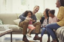 Multi-ethnic young family laughing on sofa — Stock Photo
