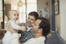 Male gay parents holding cute baby son on sofa — Stock Photo