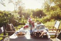 Cibo e fiori mazzo sul tavolo patio soleggiato festa in giardino — Foto stock