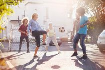Friends playing soccer in sunny summer street — Stock Photo