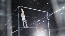 Female gymnast performing on uneven bars in arena — Stock Photo
