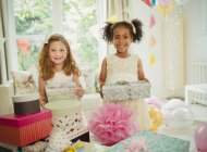 Portrait smiling girls holding birthday gifts — Stock Photo