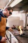 Jeweler heating metal using torch in workshop — Stock Photo