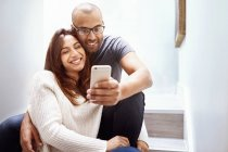 Smiling couple with camera phone taking selfie on stairs — Stock Photo