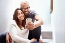 Casal sorridente com celular com câmera tomando selfie na escada — Fotografia de Stock