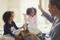Pai recebendo cartão de dia dos pais de filhas e cumprimentando na cama — Fotografia de Stock