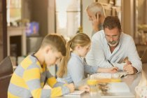 Male gay parents helping children with homework at counter — Stock Photo