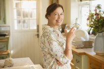 Portrait smiling mature woman drinking wine in kitchen — Stock Photo