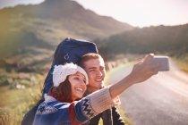 Junges Paar mit Rucksack wandert auf sonniger, abgelegener Straße und macht Selfie mit Kameratelefon — Stockfoto