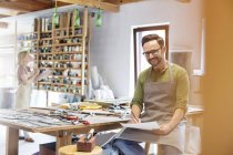 Portrait smiling stained glass artist working in studio — Stock Photo
