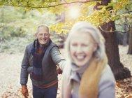 Грайливий старший пара холдингу руки в Осінній Парк — стокове фото