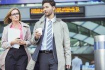 Geschäftsleute laufen und reden im Bahnhof — Stockfoto