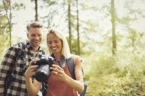 Smiling couple hiking, viewing digital SLR camera in woods — Stock Photo