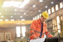 Engineer reviewing blueprints in steel factory — Stock Photo