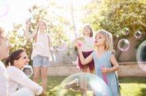 Pais assistindo filhas soprando bolhas no quintal ensolarado — Fotografia de Stock