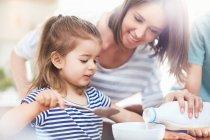 Дочка дивляться матері розливом молока в миску зернові — стокове фото