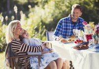 Усміхаючись ласкава сім'єю, насолоджуючись обід в Сонячний сад партії патіо таблиці — стокове фото