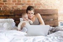 Madre con bambina utilizzando il computer portatile sul letto — Foto stock