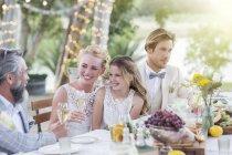 Junges paar und ihre Gäste während der Hochzeitsfeier im Garten am Tisch sitzen — Stockfoto