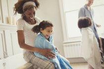 Беременная мать обертывание полотенце вокруг дочери после ванны в ванной комнате — стоковое фото