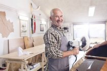 Portrait smiling, confident senior male carpenter using a buffer sander on wood boat in workshop — Stock Photo