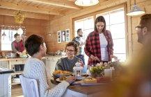 Amigos de comer y pasar un rato en la mesa de la cabina - foto de stock