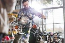 Male motorcycle mechanic working on motorcycle in workshop — Stock Photo