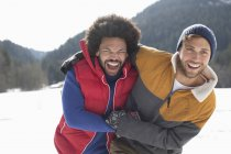 Друзі, сміючись в снігу — стокове фото