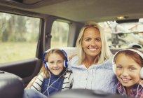 Портрет, улыбается матери и дочери носить наушники в заднем сиденье автомобиля — стоковое фото