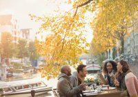 Friends laughing and eating cheesecake dessert at autumn sidewalk cafe along canal, Amsterdam — Stock Photo