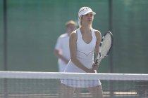 Enfoque joven mujer tenista con raqueta de tenis en la red - foto de stock
