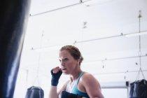 Определяется женского боксер, бокс на пробивая мешок в тренажерном зале — стоковое фото