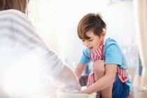 Lächelnde junge helfende Mutter backen, Teig in der Schüssel mischen — Stockfoto