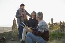 Amici maturi arrostire col barbecue e bere vino sulla spiaggia di tramonto — Foto stock