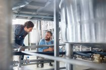 Male brewers talking vat in brewery — Stock Photo
