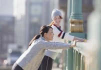 Smiling female runners stretching and talking at sunny urban railing — Stock Photo