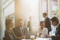 Gli uomini d'affari che lavorano al computer portatile e rivedere le pratiche burocratiche in riunione — Foto stock