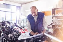 Senior male motorcycle mechanic reviewing plans in workshop — Stock Photo