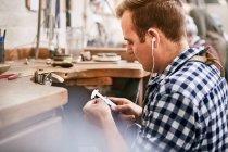 Мужчина ювелир, использующий супперы и слушающий музыку с наушниками в мастерской — стоковое фото