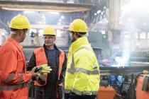Male steel workers talking in factory — Stock Photo