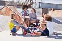 Amis en patins à roulettes et sur planche à roulettes à l'aide de tablette numérique à ensoleillé skate park — Photo de stock