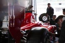 Pit équipe de travail sur la formule une voiture de course dans le garage de réparation — Photo de stock