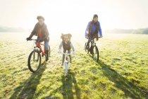 Porträt junge Familie Radfahren im sonnigen Herbst Park Rasen — Stockfoto