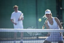 Determined young female tennis player playing tennis, hitting the ball at tennis net on sunny tennis court — Stock Photo