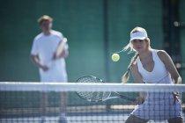 Determinado joven mujer tenis jugador jugando tenis, golpeando la bola en la red del tenis en tenis soleado - foto de stock