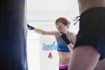 Boxe donna determinata e resistente al sacco da boxe in palestra — Foto stock