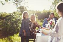 Happy family enjoying lunch at sunny garden party patio table — Stock Photo